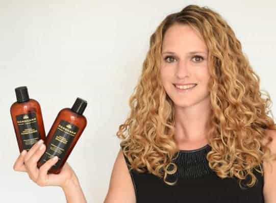 Curly haired blond holding Darshana Natural Shampoo and Conditioner.