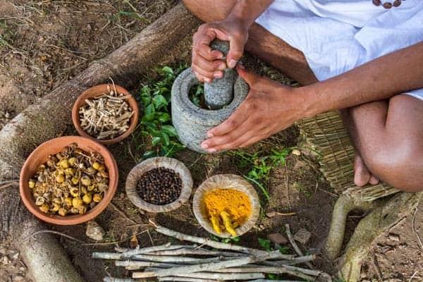 Man grinding Ayurvedic herbs