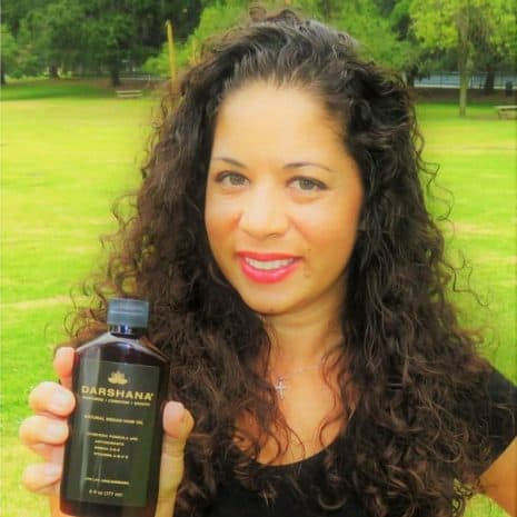 Shana holding 6 oz. Darshana hair oil bottle
