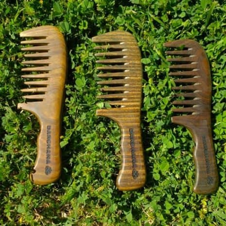 Three sandalwood combs from Darshana on green grass.